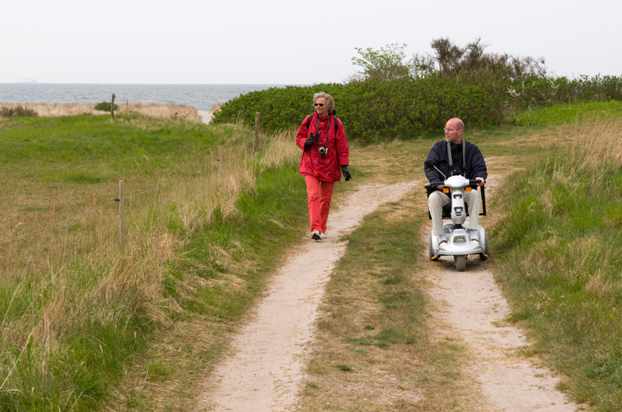 Man in a wheelchair walking with his wife near the beach